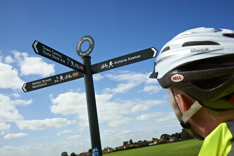A cyclist looking at a signpost in Crewe