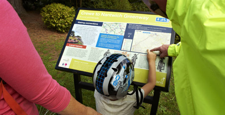 A child and parents looking at a cycle route map