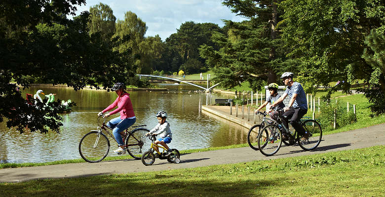 A group of cyclist riding near a lake