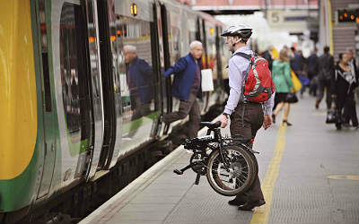 A man boards a train carrying his bicycle
