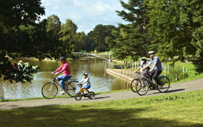Cyclists riding around a lake ion Crewe Park