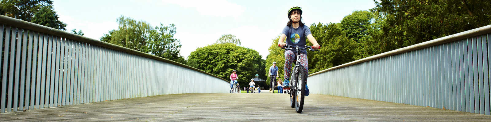 A young cyclist rides on a bridge in Crewe Park