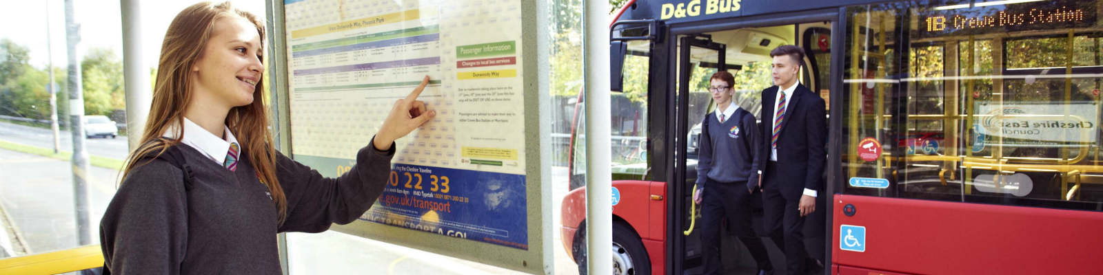A school girl looks at a bus timetable