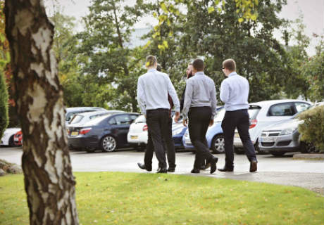 Five men walking through a car park