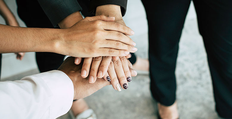 Close up of young business people putting and join their hands together. Team with stack of hands showing unity, collaboration and teamwork